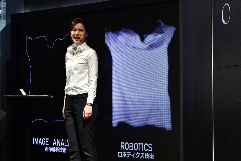 This photo taken on October 7, 2015 shows a model demonstrating a prototype of an automatic laundry folding machine during Ceatec, Asia's largest electronics trade show in Chiba, suburban Tokyo. Japan's Panasonic, Seven Dreamers and Daiwa House are expecting to commercialise automatic washing, folding, and clothes-sorting machines in 2017. AFP PHOTO / Yoshikazu TSUNO